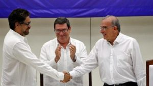 Ivan Marquez (R, FARC) and Colombia negotiator Humberto de la Calle (L) shake hands while Cuba's Foreign Minister Bruno Rodriguez looks on, Havana, Cuba, Aug. 24, 2016 (photo by Reuters)