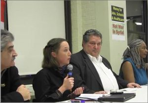 Eva Bartlett (with microphone) speaking to public forum in New York city on Dec 2, 2016 (screenshot of Hands Off Syria Coalition video)