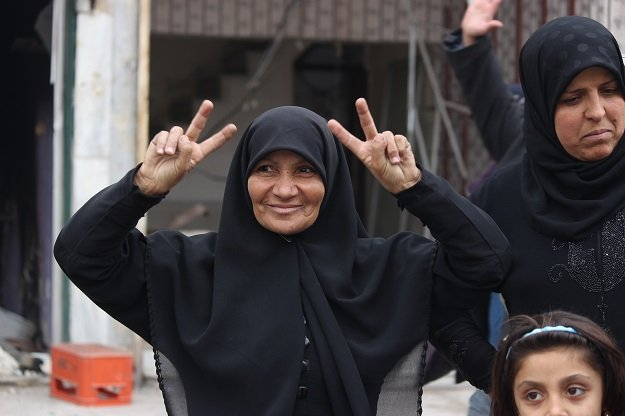 Hanano, East Aleppo, December 2016. A woman who had been liberated from terrorist occupation hours previously, gives the victory sign.